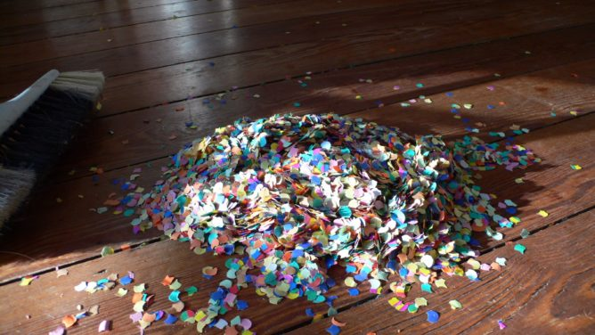 Konfetti und Besen auf Holzboden